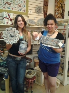 Volunteers Jessica (L) and Teresa with some of our coolest recycled newspaper products. The Women's Multipurpose Co-op also makes products from juice boxes, candy wrappers and chip bags.